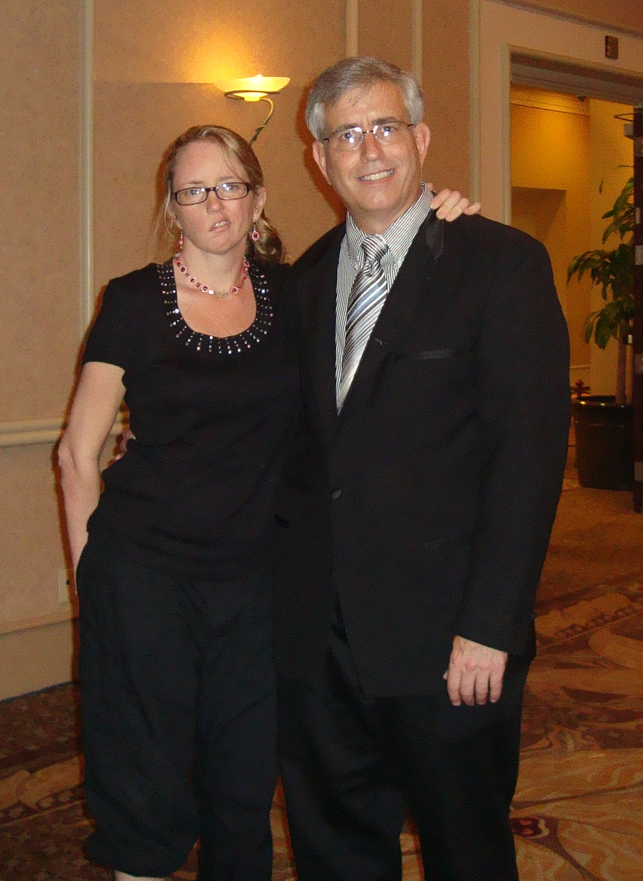 Cindy Reese dressed up in black pantsuit standing on left arm in arm with Bill Reese in suit standing on right